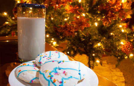 lighted: Glass of milk and cookies waiting by the Christmas tree Stock Photo