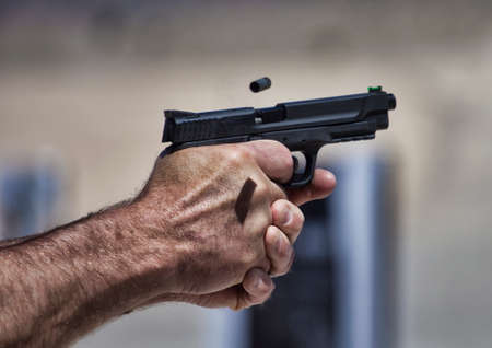 Brass flying from a handgun held tightly by the shooter Stock Photo