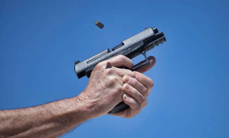 Empty casing flying out of a semi automatic pistol Stock Photo
