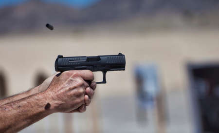 Pair of hands holding a handgun as it is being shot Stock Photo