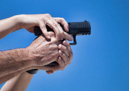 grip: Firearm instructors hands adjusting the handgun grip of a student