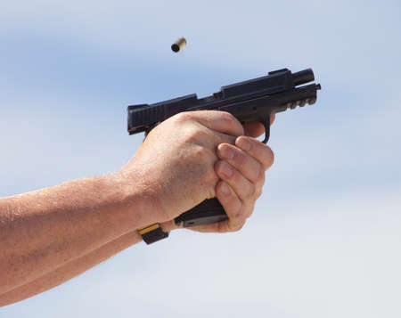 Handgun with brass ejecting just after being shot