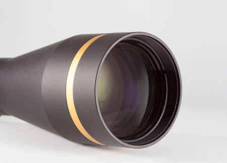 Large front lens on a rifle scope on white
