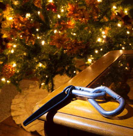 Carabiners and piton on table with a Christmas tree behind Stock Photo