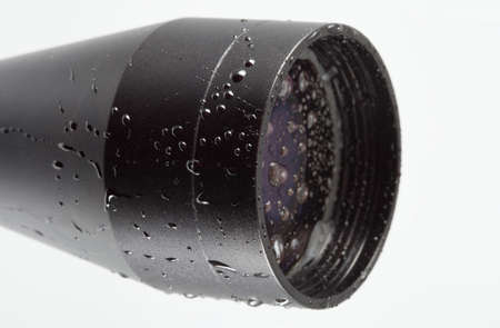 Objective lens on a rifle scope covered in water