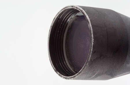 Objective lens on a rifle scope covered in frost and water