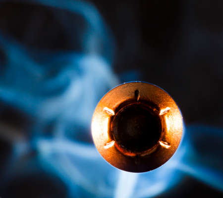Copper plated hollow point bullet with smoke coming at the viewer Stock Photo