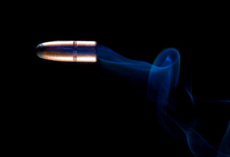 Copper plated bullet with smoke trailing on a black background