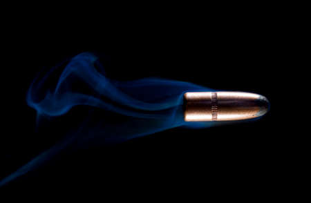 Blue smoke behind a bullet on a black background
