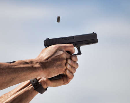 Brass ejected and flying near a pistol while shooting