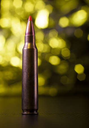 Cartridge that is used in an AR-15 with a yellow background Stock Photo