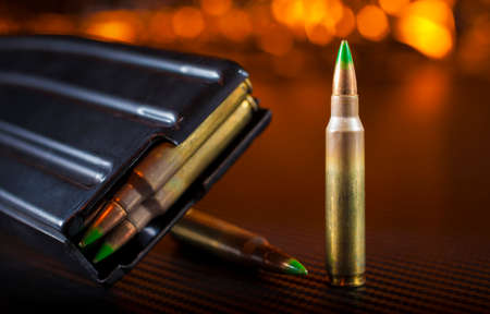 Ammo that fits in an AR-15 and magazine with orange background Stock Photo