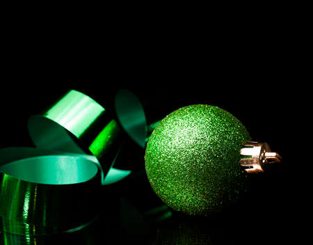 Green ribbon and shiny green Christmas ornament on black Stock Photo