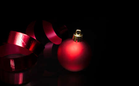 Red ribbon and Christmas ornament on a black background Stock Photo