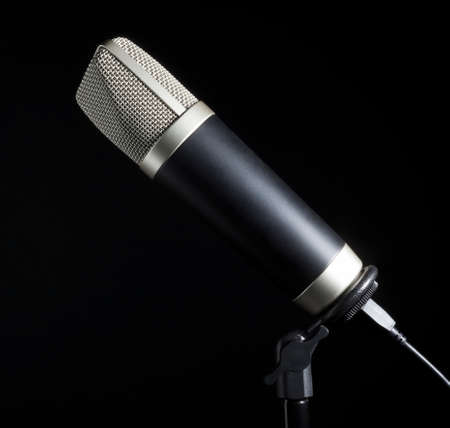 Silver meshed microphone on a stand with a black background Stock Photo