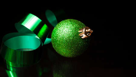 Green Christmas ornament and matching ribbon on a black background
