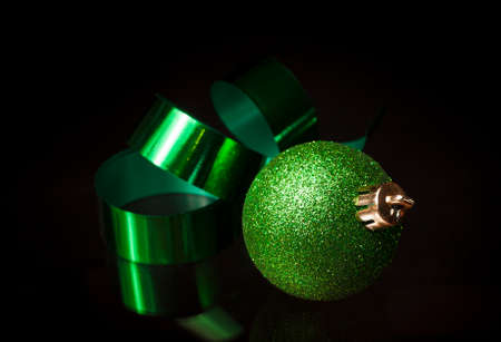 Green Christmas ornament and ribbon on a black background