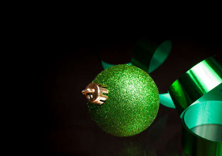 Green ribbon and a Christmas ornament on a black background Stock Photo