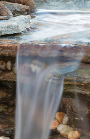 Water flowing over a small cascade with lots or rocks Reklamní fotografie