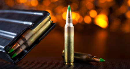 M855 ammunition and metal magazine for AR-15s with an orange background Stock Photo