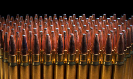 Rifle bullets fora 338 in rows with a black background