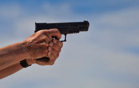 Polymer framed handgun with finger on the trigger and clouds behind