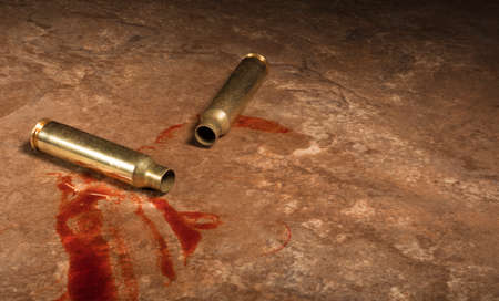 Empty shells from an AR-15 and blood on a beige floor Stock Photo