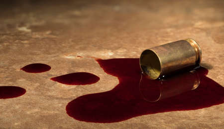 Beige floor tile with empty handgun brass laying on it with blood Stock Photo