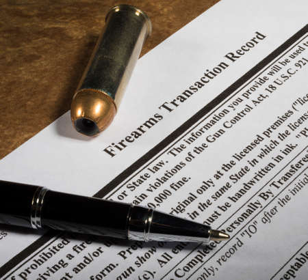 Top of the FBI NICS background check to buy a gun with a pen and cartridge