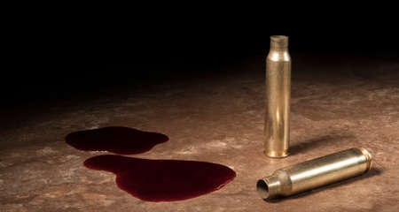 Blood and two empty AR-15 shells on a tan floor Stock Photo