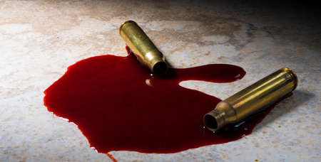 Empty rifle cartridlges and blood on a beige floor Stock Photo