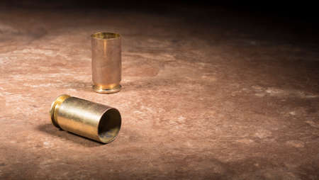 Empty brass ejected from a 45 caliber pistol on a brown background Banco de Imagens