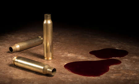 Three empty AR-15 casings with blood on a brown floor Stock Photo
