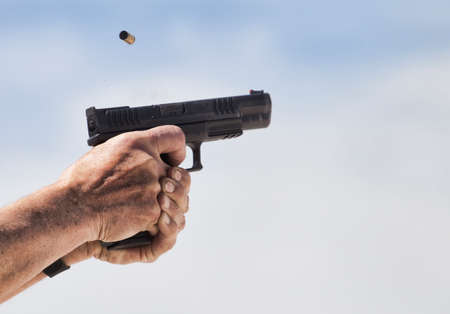 Empty brass ejected from a semi automatic pistol with sky behind