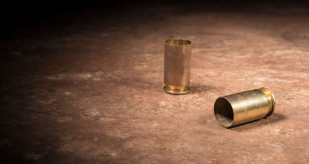 Empty hulls from a 45 caliber semi auto handgun on a beige floor tile Banco de Imagens