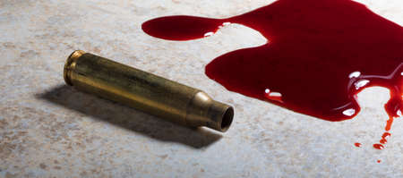 Blood and an empty assault rifle cartridge ont he floor Stock Photo