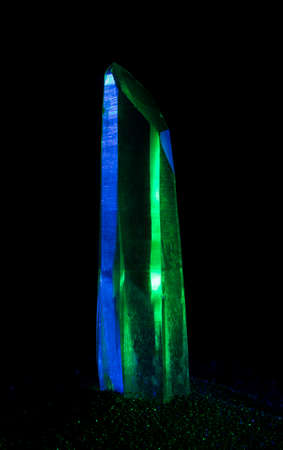Blue and green lights on a quartz crystal in black sand