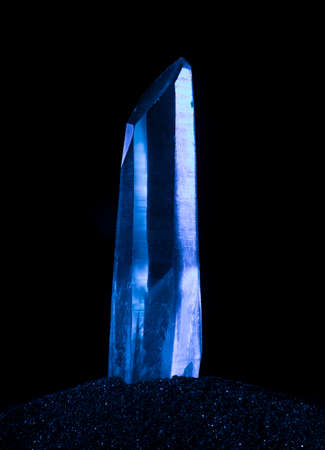 Quartz crystal on a black background with blue light