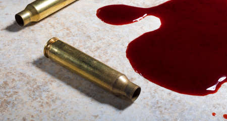 Blood on the floor with empty assault rifle ammunition nearby Stock Photo