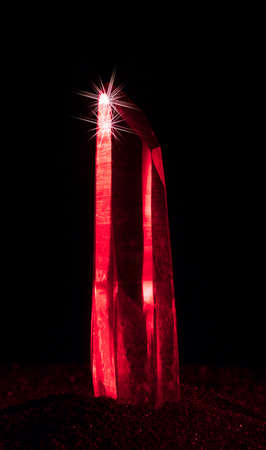 Crystal of quartz with red light on a black background