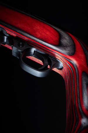 Trigger and safety on a rifle stock with laminated red wood