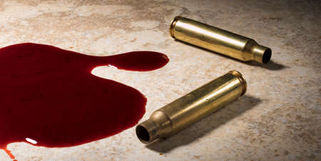 Floor with blood in a pool and empty AR-15 brass casings Stock Photo