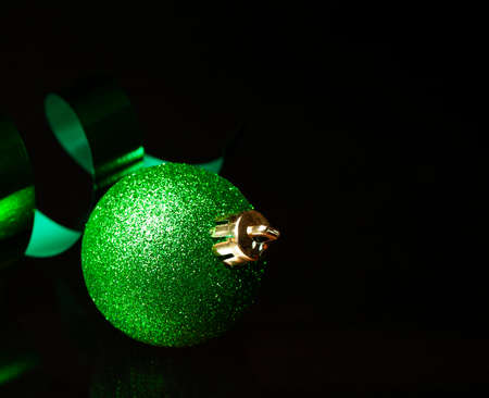 Green Christmas ornament on ribbon on a black surface Stock Photo