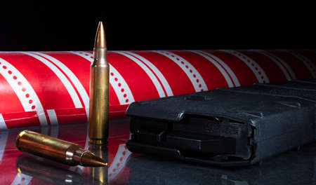 Red Christmas wrapping paper with ammunition and a polymer magazine Stock fotó