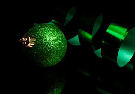 Green Christmas bulb and ribbon on a black background Stock Photo