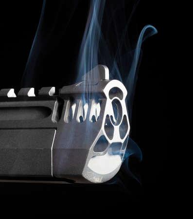 Humo procedente de una pistola sobre un fondo negro Foto de archivo