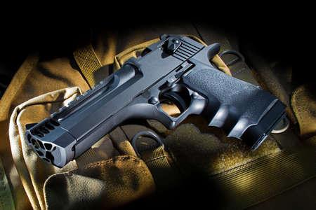 Black semi auto handgun on a beige nylon bag 版權商用圖片