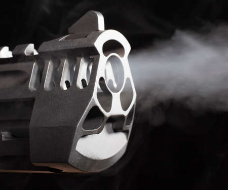 Smoke blowing out of a pistol barrel on a black background