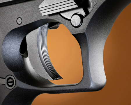 Trigger on a semi auto pistol on a beige background