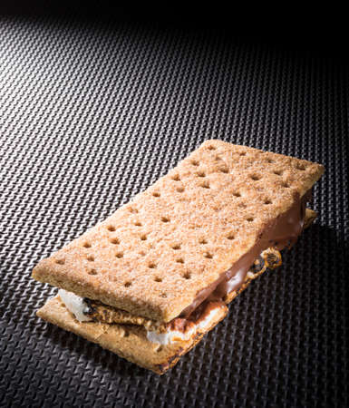 Smore on a textured black background with light coming from behind